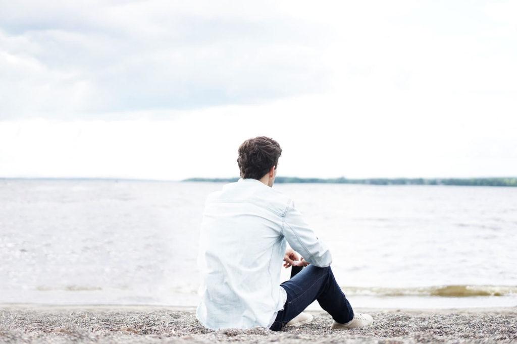Mężczyzna siedzi na plaży