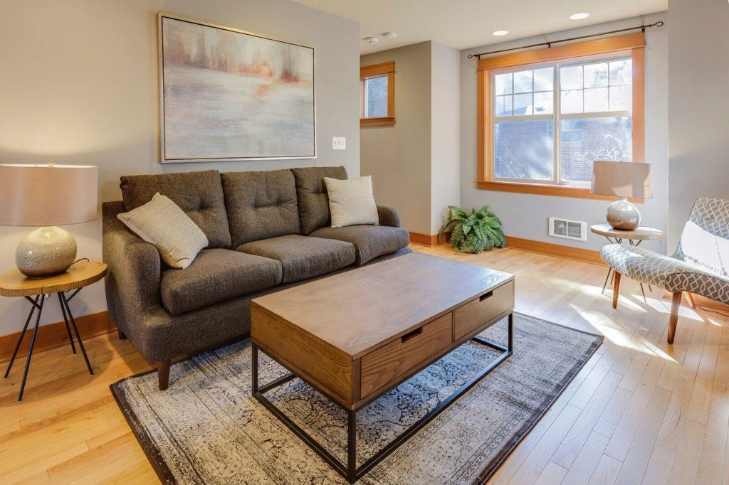Salon z szarą kanapą i dywanem